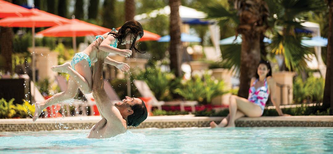 Family playing at Four Seasons Orlando swimming pool