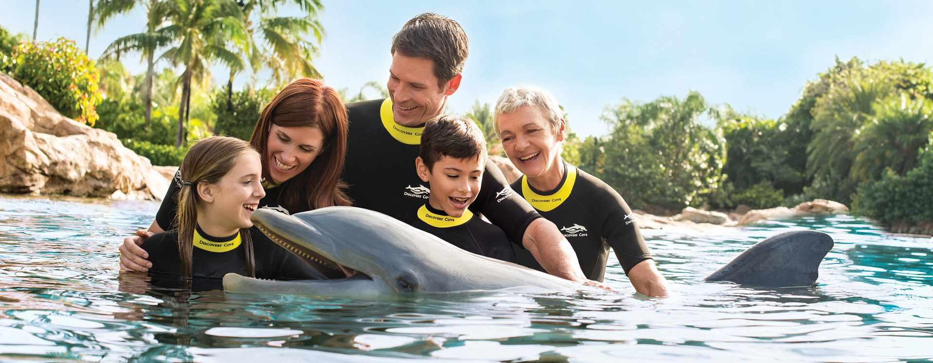 Família com cinco pessoas posando para foto com um golfinho em uma lagoa