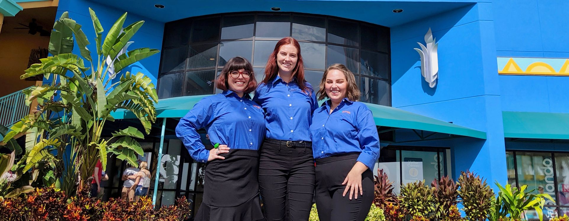 Three young ladies that represent ambassadors of MORlando standing together in front of the Visit Orlando Official Visitor Center on International Drive