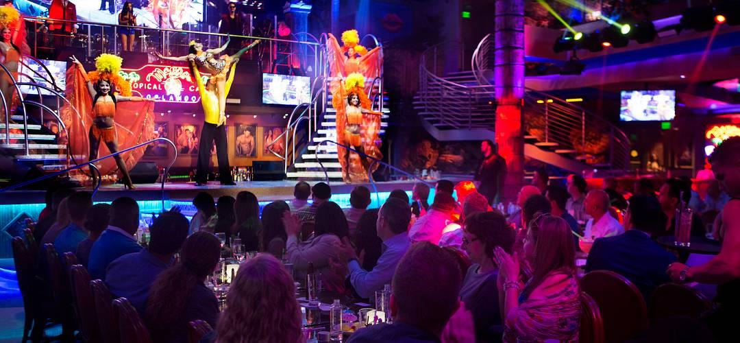 Grupo de personas cenando y presenciando un espectáculo de baile dentro del establecimiento Mango's Tropical Cafe