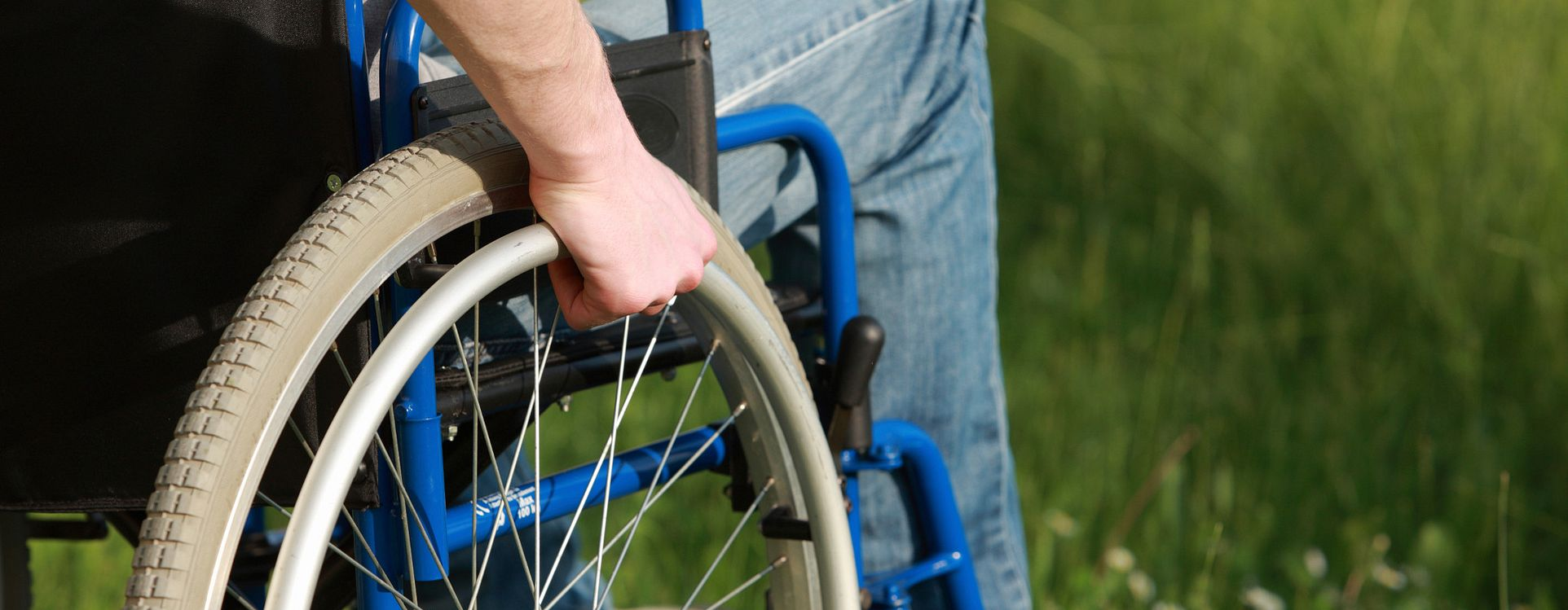 a man's arm gripping a wheelchair handrim