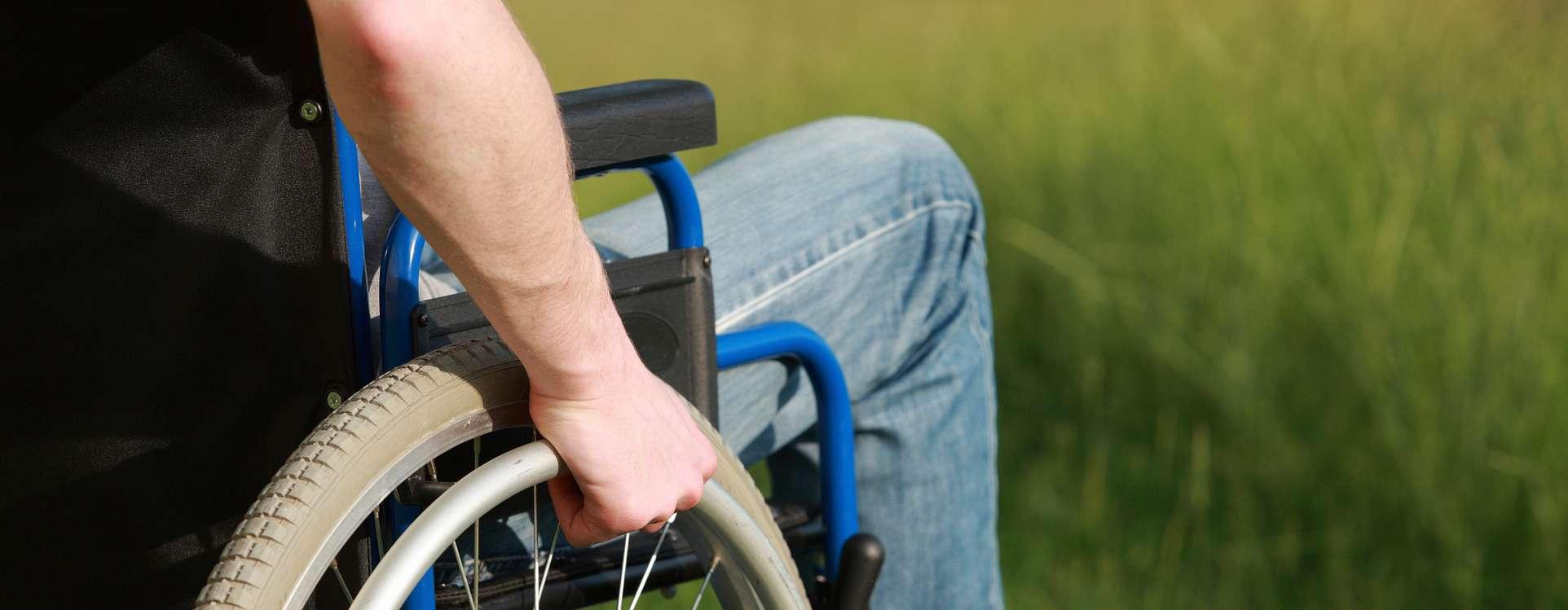 a man's arm gripping a wheelchair handrim