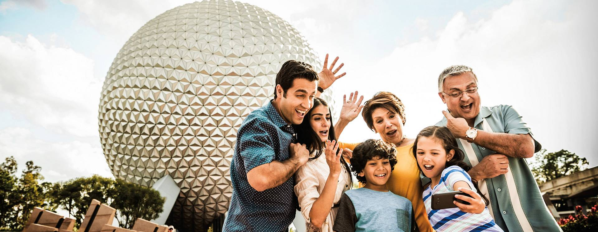 Family posing for a selfie in front of the Spaceship Earth globe at Epcot