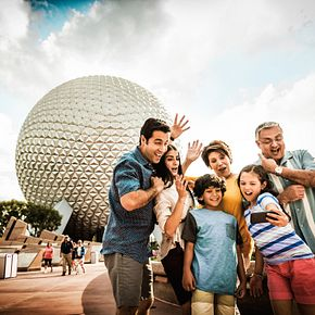 A family posing for a photo at the entrance of Epcot