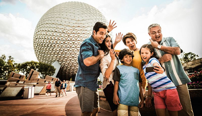 An extended family taking a group picture in front of Spaceship Earth at Epcot.