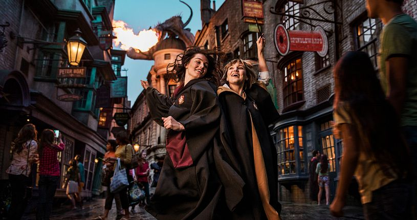 Two young ladies prancing about in their wizarding robes on Diagon Alley, with a fire-breathing dragon in the background.