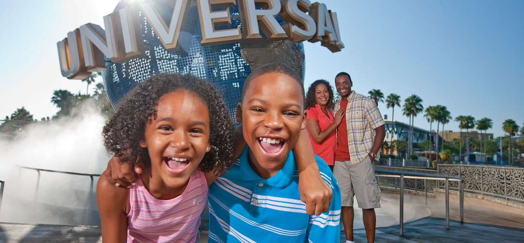 A family playing and posing in front of the Universal Orlando globe.