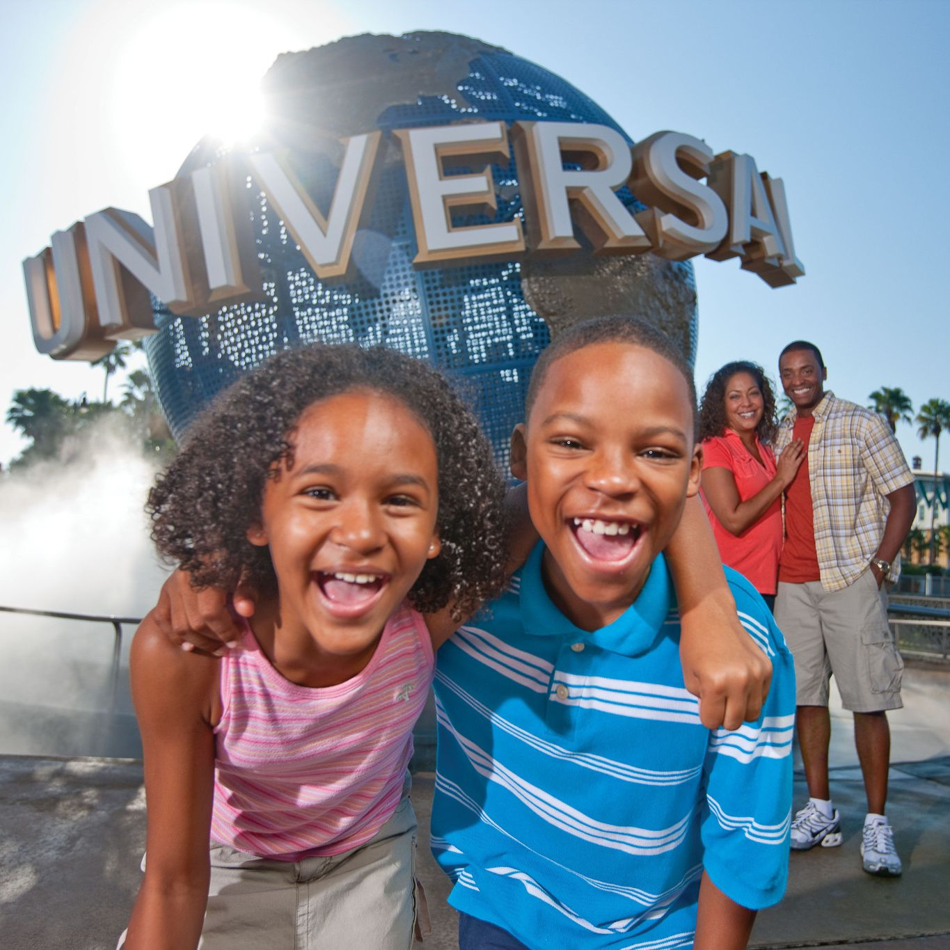 Family posing for a photo in front of the famous globe at Universal Orlando Resort.