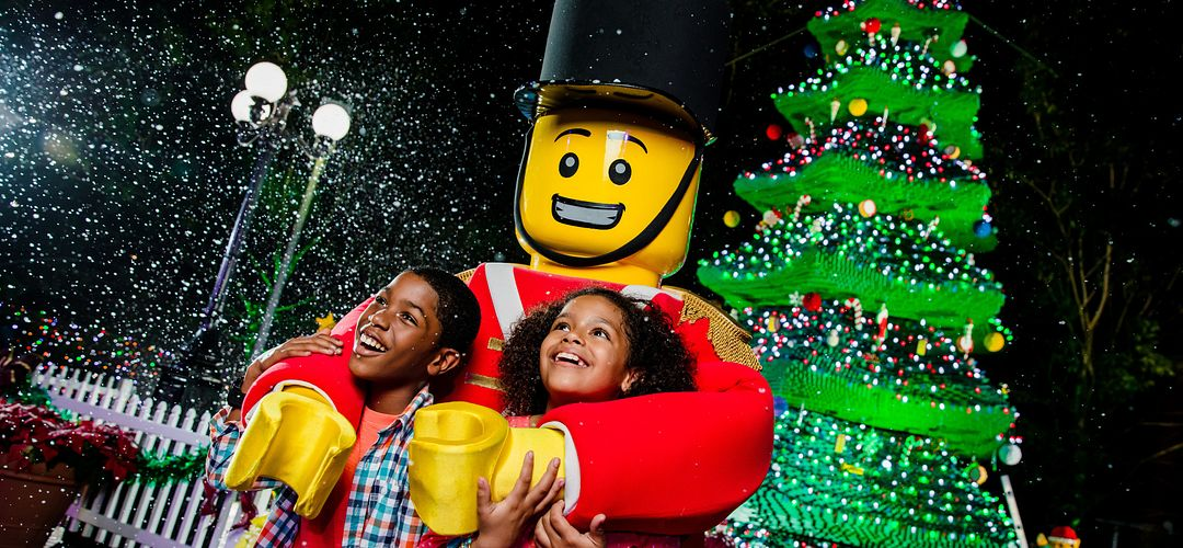 Children smile with a LEGO man during Holidays at LEGOLAND Florida Resort.