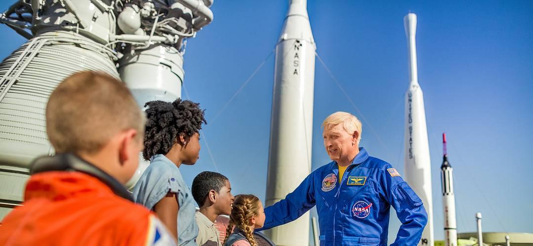 Astronauta hablando a un grupo de niños en el Rocket Garden en el Kennedy Space Center Visitor Complex