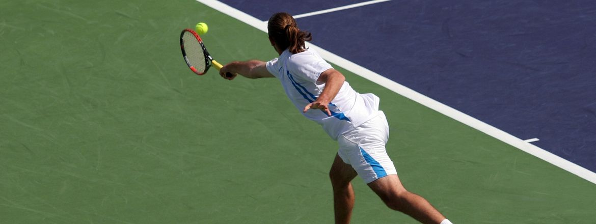 Tennis player lunging after a ball with a backhand