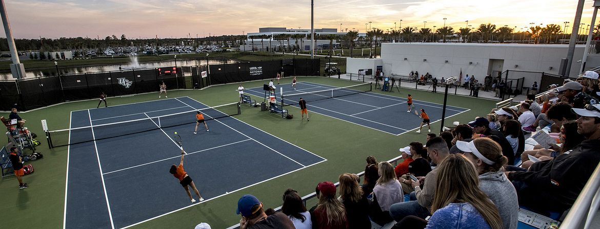 Spectators watching a tennis competition on the collegiate courts at the USTA National Campus in Orlando