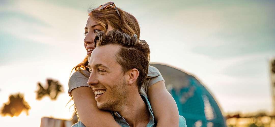 Una pareja frente al globo terráqueo de Universal Studios en Orlando, Florida.