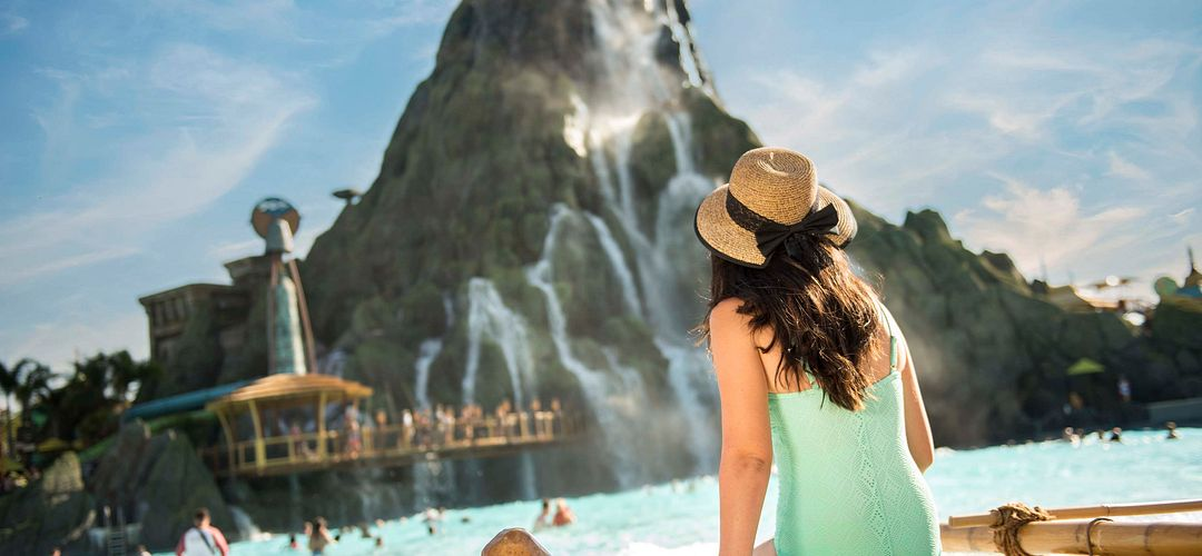 A young girl sitting on the shore of Waturi Beach at Universal's Volcano Bay.