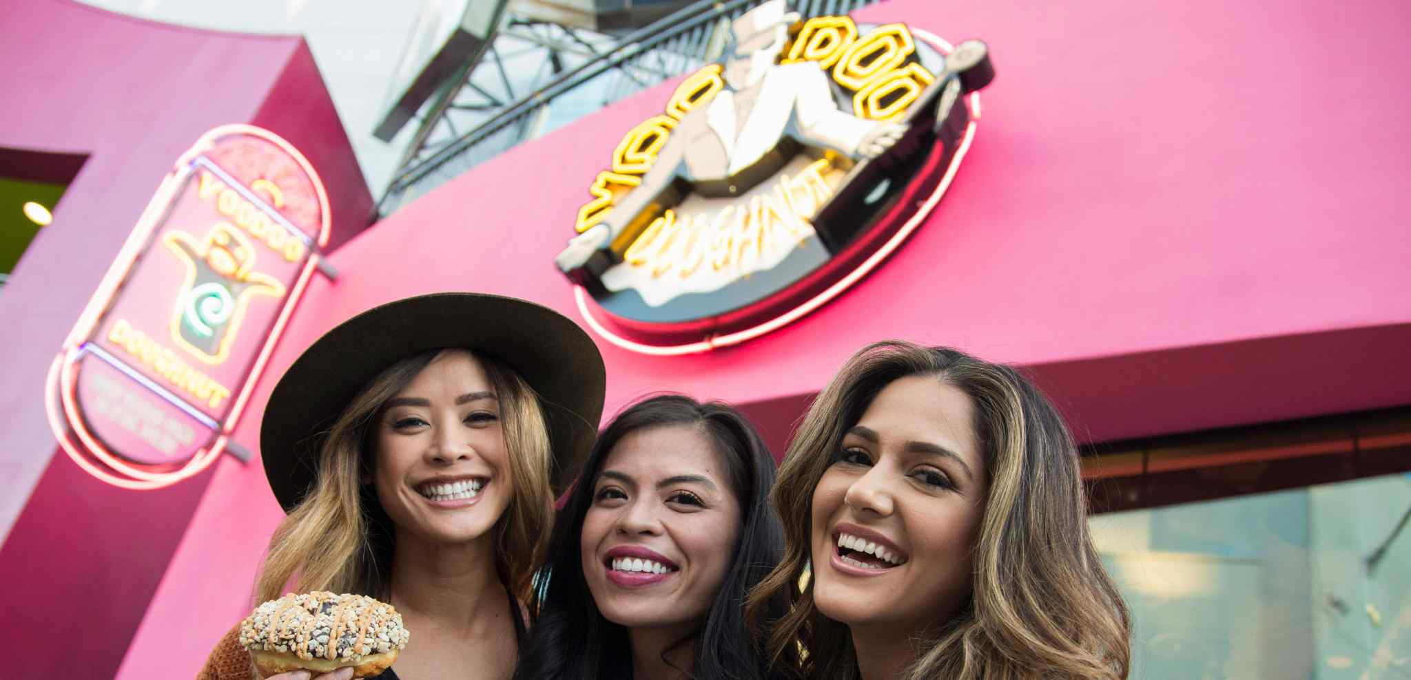 Three ladies posing in front of Voodoo Doughnut shop holding donuts
