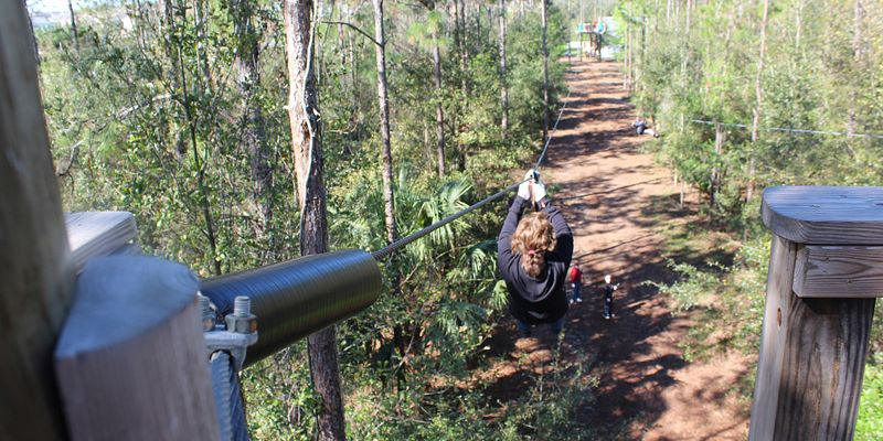 Woman on a zip line at Orlando Tree Trek