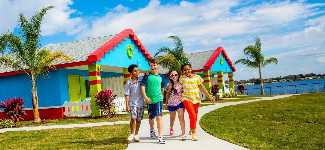 Niños caminando cerca de unas cabañas en Legoland Florida.