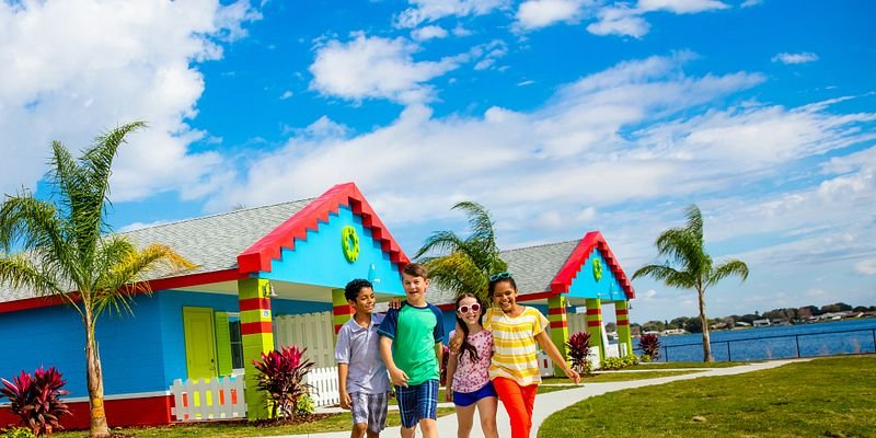 Four kids walking with lego bungalows behind them