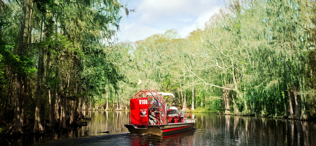 Spririt of the Swamp Airboat Rides carries passengers on a red airboat as it glides over calm waters surrounded by cypress trees.