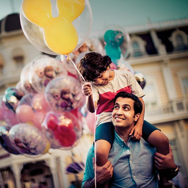 A father and son with Mickey balloons at the Magic Kingdom park