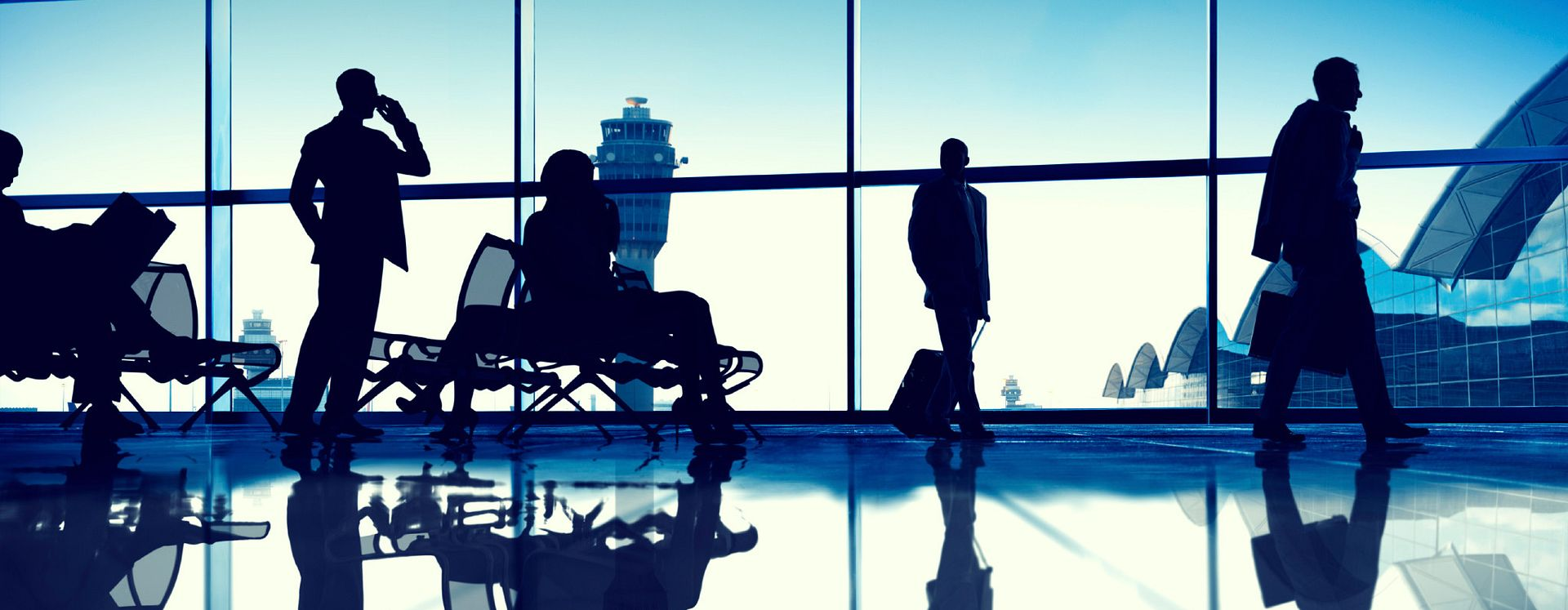 Silhouettes of travellers in an airport