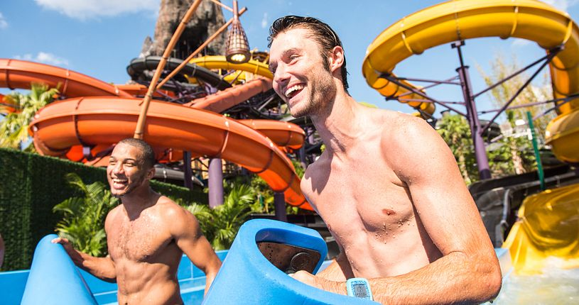 Two men walking towards Volcano Bay's Punga Racers waterslide