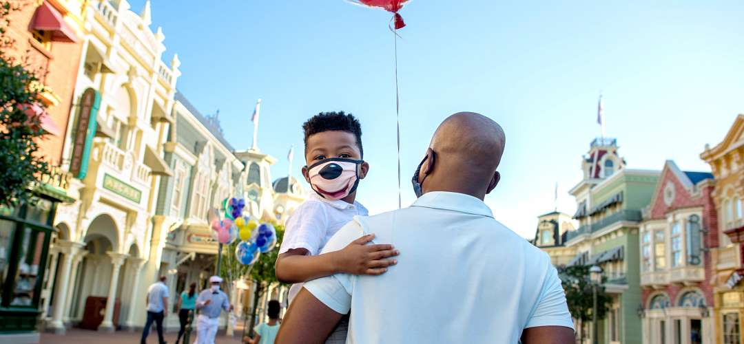 A father holding his son while walking in the Magic Kingdom. Both are wearing face masks.