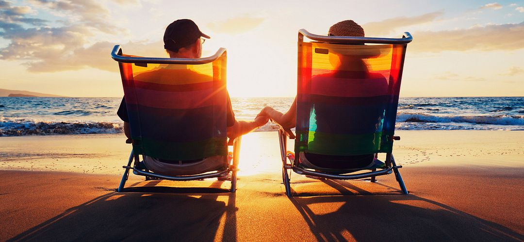 Couple holding hands while enjoying a beautiful sunrise on the beach