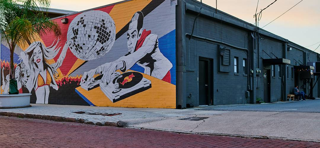 Colorful mural of a DJ playing music with people dancing on a building wall at Mills 50