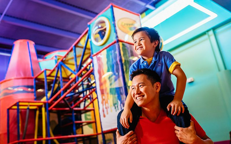 Son on father's shoulders at the Crayola Experience playground
