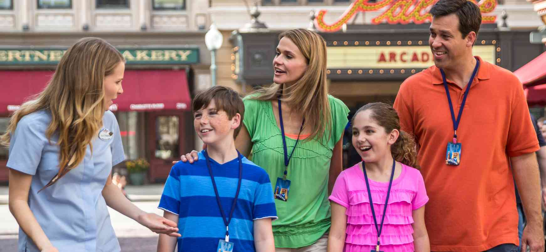 A family of four being guided inside a theme park by a Universal Studios employee