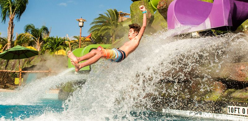 A kid dropping into a pool from the Ohno Ohya slide