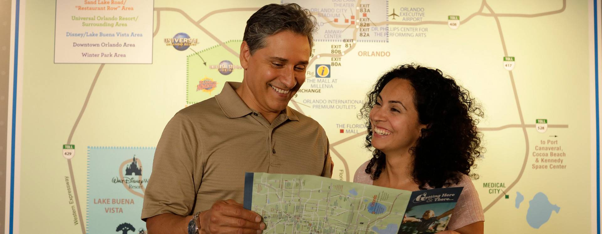 A smiling couple holding an Orlando brochure with a map
