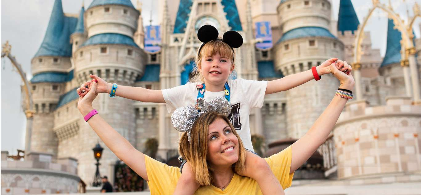 A mother lifts her child with Cinderella's Castle in the background.
