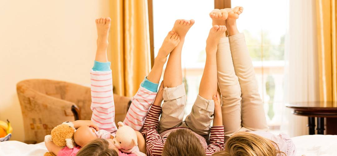 Children lying down on a bed with legs in the air