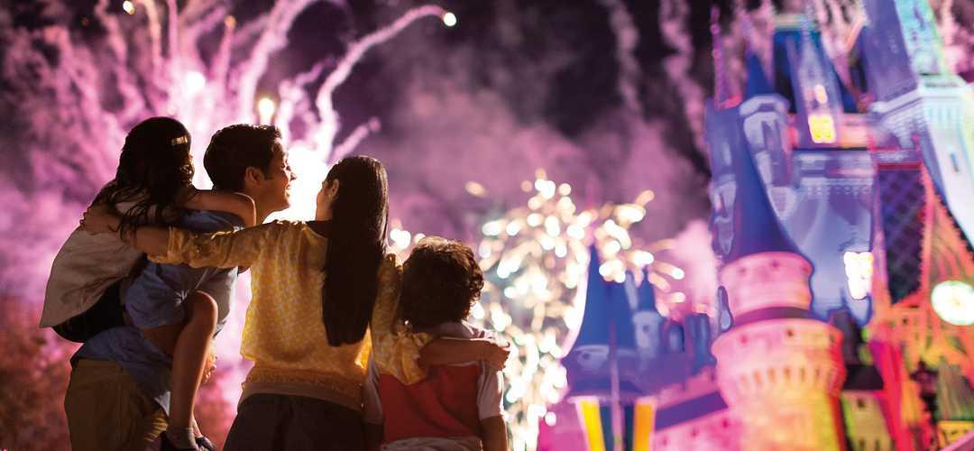 Una familia muy unida disfruta de la deslumbrante exhibición de fuegos artificiales en el Cinderella Castle en Disney's Magic Kingdom