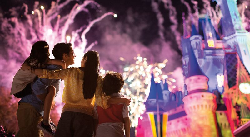 A close family enjoys the dazzling display of fireworks at Cinderella's Castle in Disney's Magic Kingdom.