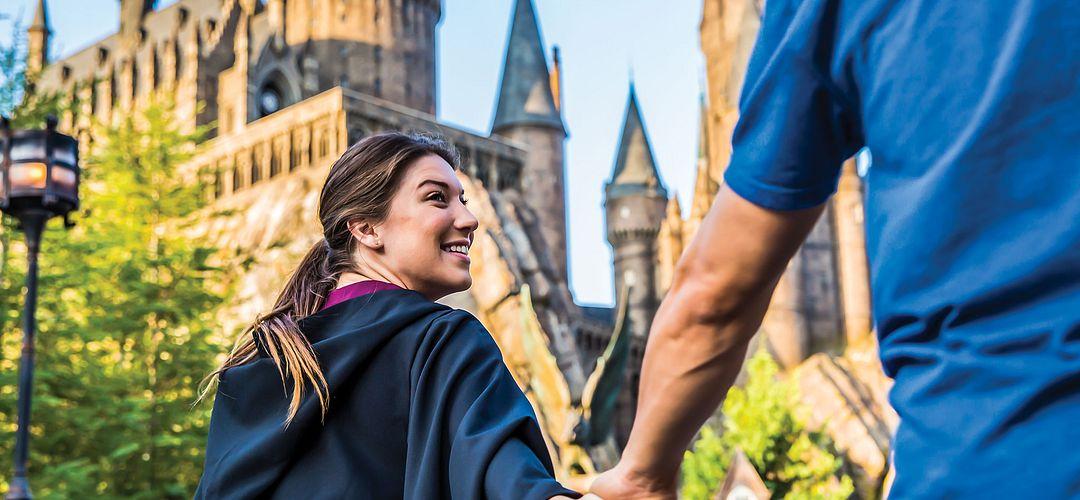 pareja agarrada de la manoy caminando con emoción hacia Hogwarts Castle en Islands of Adventure