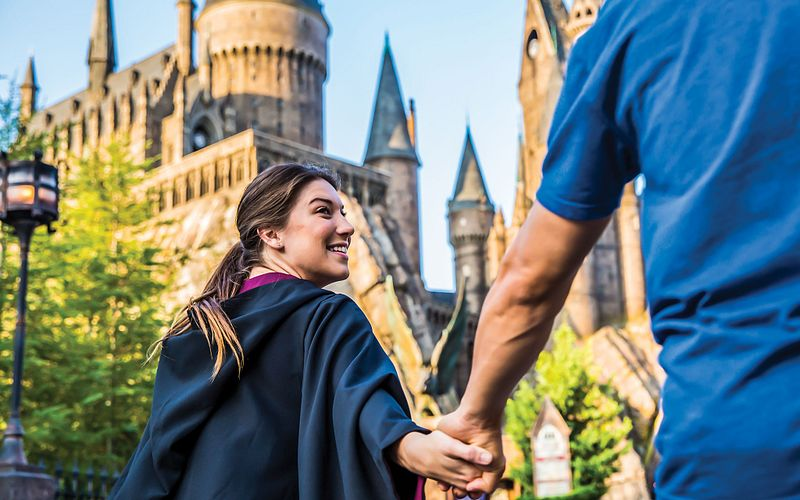 Couple holding hands and excitedly walking towards Hogwarts Castle at Islands of Adventure.