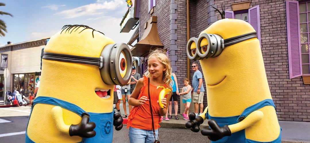 Three friends posing with two Minions at Universal Studios Florida