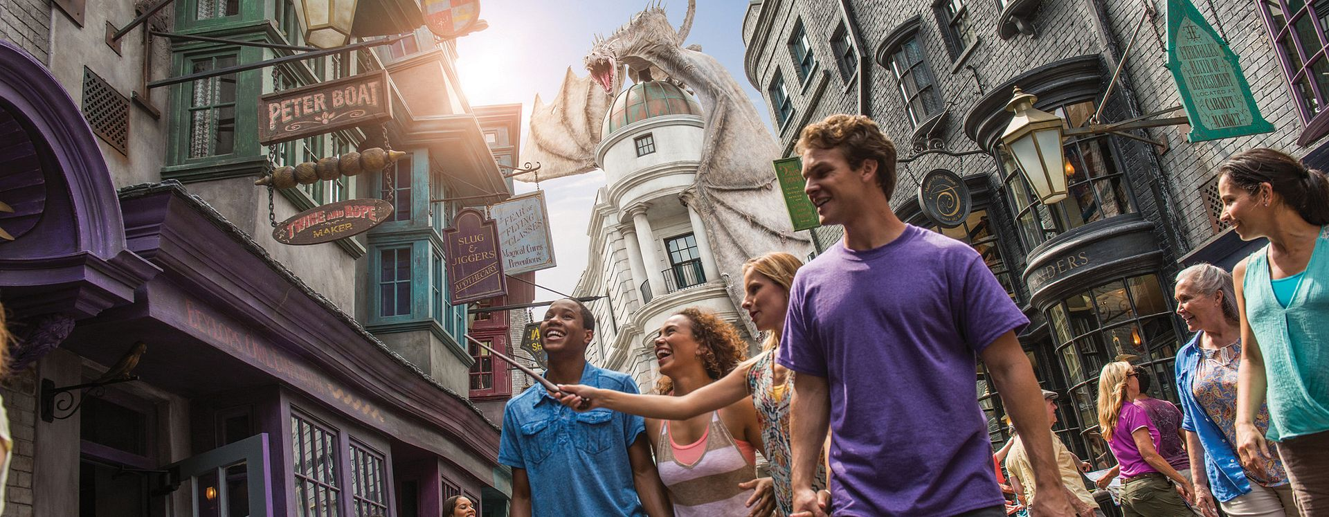 Four friends walking in Diagon Alley in The Wizarding World of Harry Potter with the dragon in the background