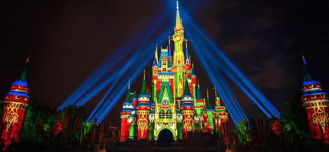 A nighttime shot of holiday projections on the Cinderella Castle inside the Magic Kingdom