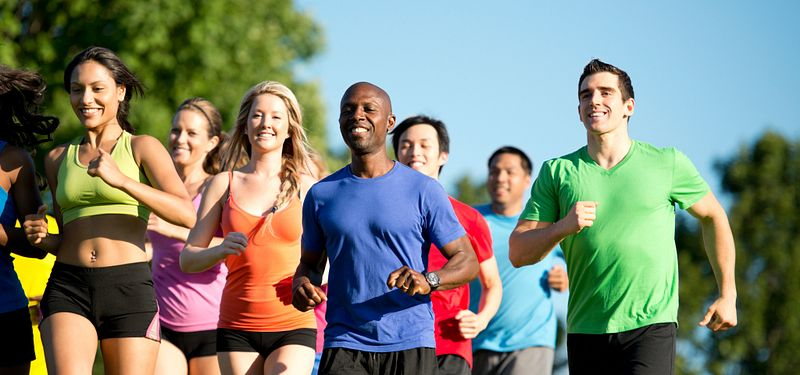 A group of men and women jogging on a sunny day