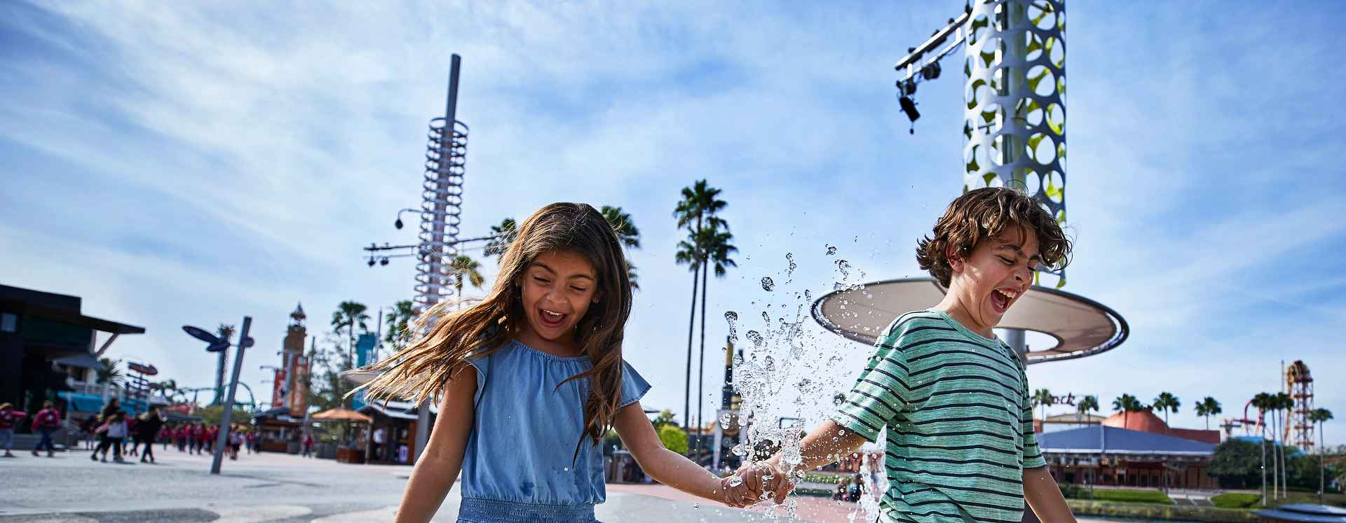 Young children holding hands and having fun in a splash pad at Universal's CityWalk.