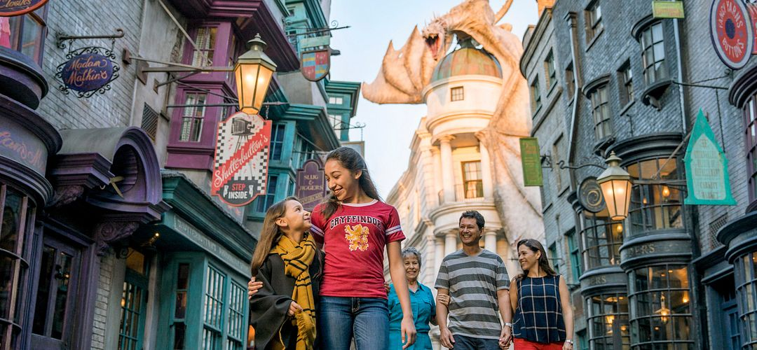 Two young ladies walking in front of their parents and grandmother in Diagon Alley™ with a dragon perched on top of a building in the background.