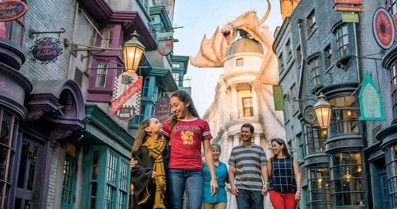 Two young ladies walking in front of their parents and grandmother in Diagon Alley with the dragon in the background.
