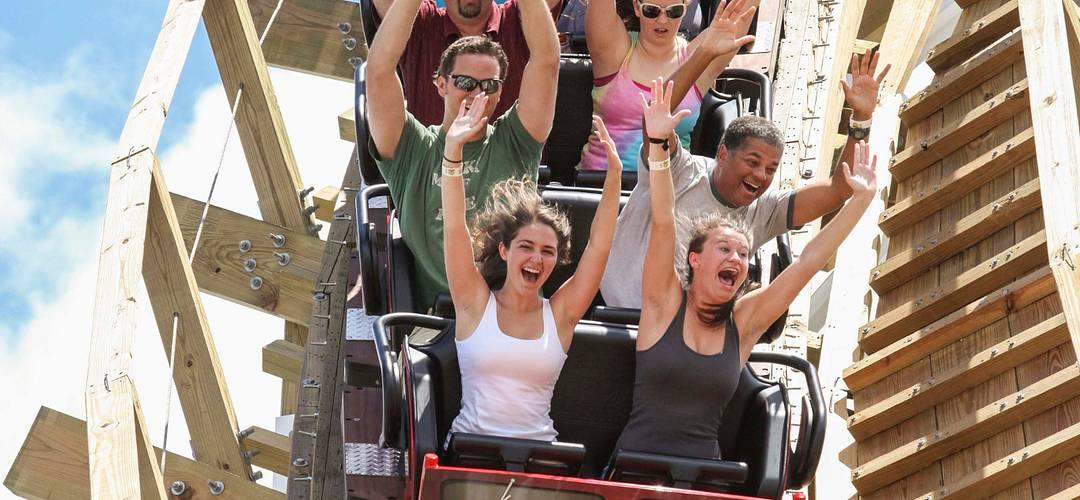 Personas con los brazos en alto montados en una montaña rusa de Fun Spot