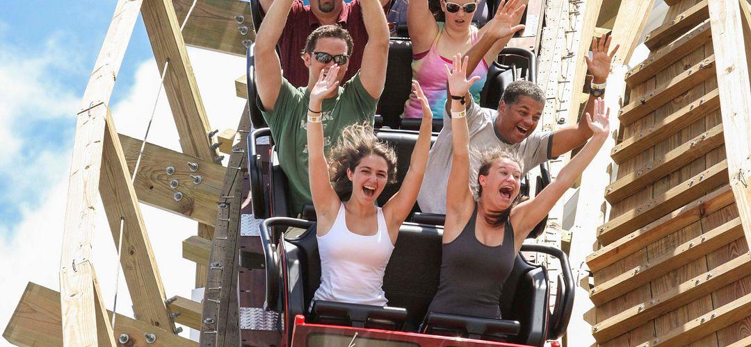 um grupo de pessoas com os braços levantados em uma montanha-russa do Fun Spot