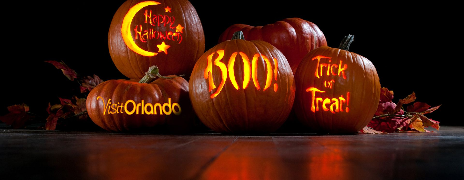 Pumpkins piled on top of each other with different sayings carved out for Halloween in Orlando