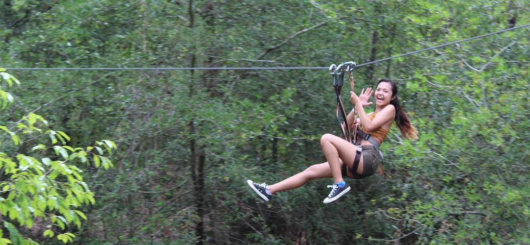 A girl ziplines through trees in Orlando